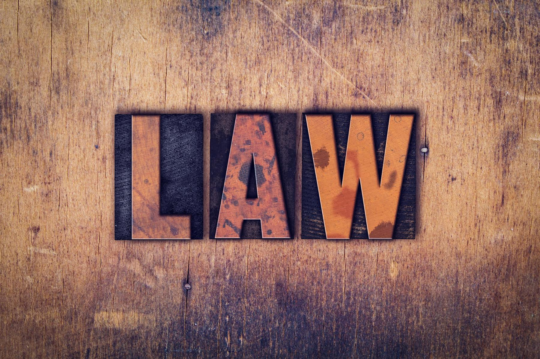 "The word ""Law"" written in dirty vintage letterpress type on a aged wooden background."